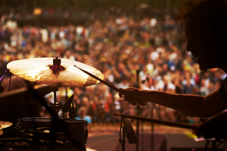 Cropped shot of a drummer playing in front of a large crowd at an outdoor music festival